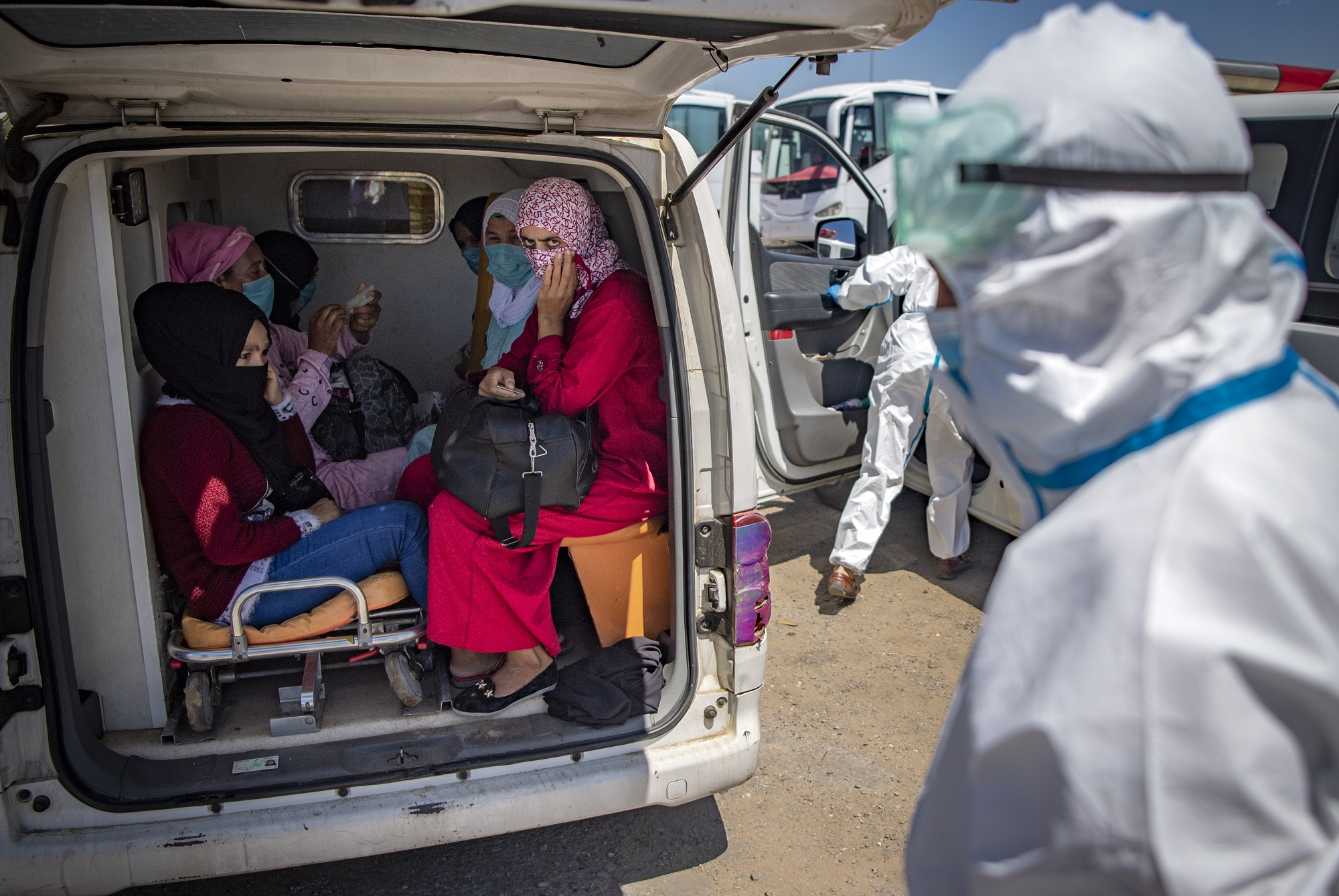Moroccans, who tested positing for Covid-19, arrive in a parking lot in the town of Moulay Bousselham, north of the capital Rabat, on June 20, 2020, ahead of being transferred to a medical center in another city. - Morocco reported a record single-day rise in novel coronavirus cases on Friday after an outbreak was discovered in red fruit packing plants in a rural area northeast of Kenitra city, prompting Rabat to tighten restrictions in the region.  The North African kingdom reported more than 500 cases on Friday, mainly in Kenitra, having recorded on average fewer than 100 new COVID-19 cases daily since confirming its first cases in early March. (Photo by FADEL SENNA / AFP)