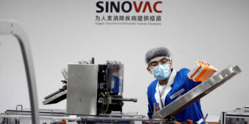 FILE PHOTO: A man works in the packaging facility of Chinese vaccine maker Sinovac Biotech, developing an experimental coronavirus disease (COVID-19) vaccine, during a government-organized media tour in Beijing, China, September 24, 2020. REUTERS/Thomas Peter/File Photo