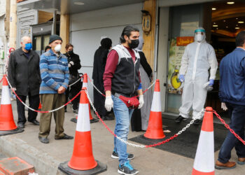 Customers wearing face masks and gloves queue outside a supermarket, during a lockdown to prevent the spread of coronavirus disease (COVID-19) in Beirut, Lebanon April 6, 2020. REUTERS/Mohamed Azakir - RC23ZF91BZ0E